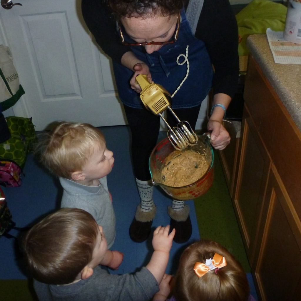 toddlers practice cooking with support from a teacher