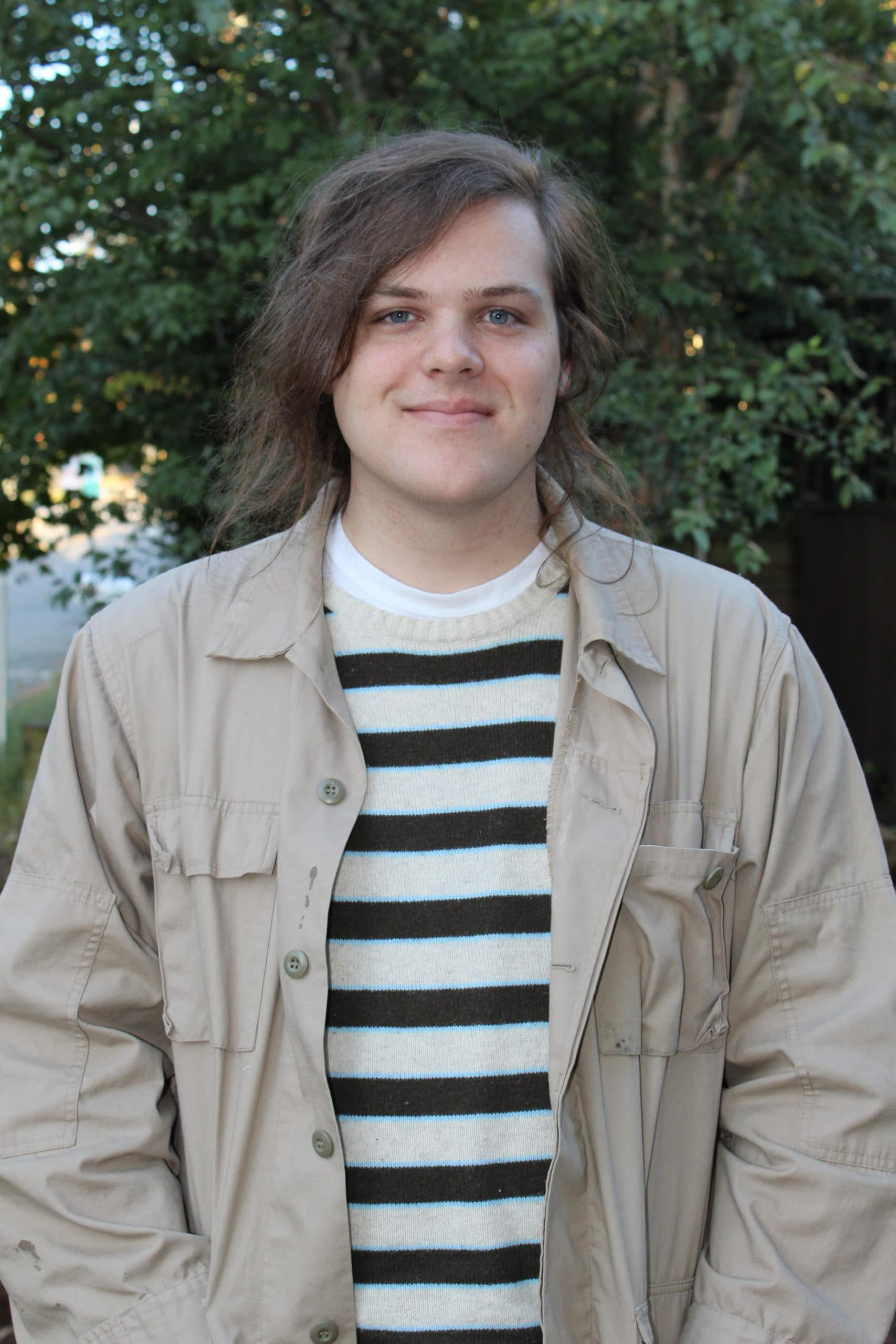 Shane smiles with no teeth, tree, stripes, jacket