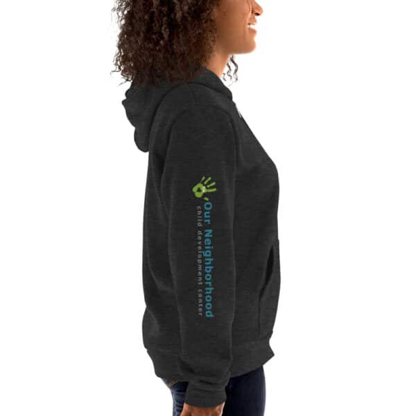 """side view of dark gray hoodie, zip up, text reads """"our neighborhood"""" on the side of the arm"""
