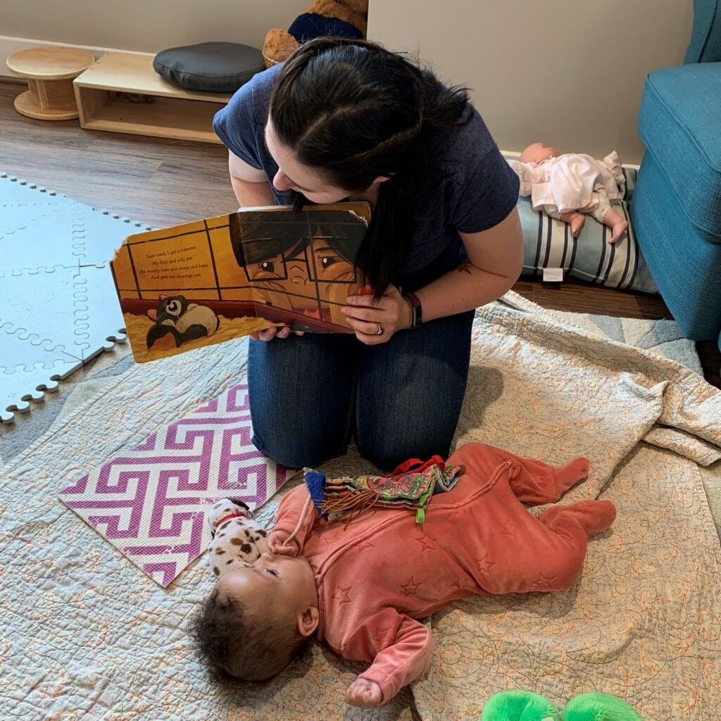 Responsive infant teacher reading with young baby on a blanket.